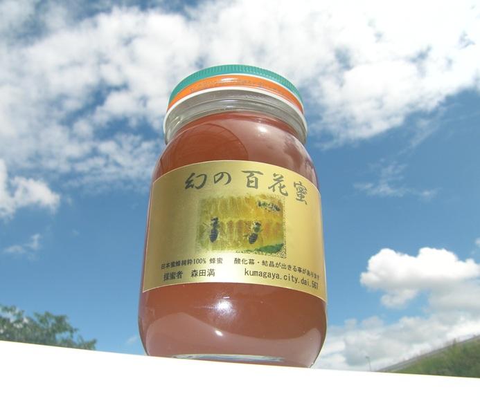 """*百花蜜の性質  西洋蜜蜂の蜂蜜は透明ですが、日本蜜蜂の蜂蜜は""""琥珀色""""をしております。西洋蜜蜂では、蜂が花蜜を集めた後に短期間に採蜜するためです。  一方、日本蜜蜂は時間を掛けて巣作りし、花粉(幼虫の蛋白源)を貯めた巣にも蜜をためるため、その色が蜜に含まれ、""""琥珀色""""となります。決して不純物によるものではありません。  日本蜜蜂の蜂蜜は個性ある風味を保持させるために""""生""""です。西洋蜜蜂の蜂蜜(一部)のように加熱処理は全くしません。そのため、保存期間中に表面に白い泡・固形物が観察される事があります。これは蜂蜜の成分(ショ糖=果糖+ブドウ糖)が分解してブドウ糖が析出するためで、食するには全く問題がありません。このような現象は、蜂が樹木の花よりも草花の花蜜を集める飼育環境下では良くみられます。気になるようでしたら、湯煎あるいは電子レンジで2-3分チンすれば消失します。また蜂蜜が固形化した場合も同様にすれば液化します。  *蜂蜜の作り方 西洋蜜蜂の飼育では蜜が詰まった人工巣を遠心分離機で回し、機械的に採蜜します。 一方、日本蜜蜂の蜜は、蜂が作った貯蜜圏巣(蜜を蓄えた部分)を細かく砕き、ステンレスのザルに乗せ、時間を掛けて自然に蜜を垂らします。その後、細かい巣のかけらを""""さらし""""などで数回ろ過して除きます。このような自然の方法で蜜を精製するため、日本蜜蜂の蜜は""""垂れ蜜""""と呼ばれています。このようなステップをふむ事により、蜂蜜の成分としては、蜜、ビタミン、ミネラル、アミノ酸、抗酸化物、有機酸および巣の成分(高級脂肪アルコールなど)を含み、胃、肝臓などに効能があり、また精力剤として良いとされております。"""
