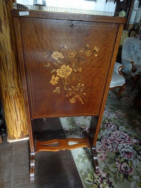 材質:マホガニー<br />年代:1900年代<br />サイズ:W500xD420xH1050<br /><br />なんだか聞きなれない名前の家具ですが、元々はフランス家具の名前です。一般的なエスクリトアはビューローのようなものですが、ビューローと違うのはななめの板を下ろして天板にするのではなく、垂直の板が倒れてきて物書き様の天板になるというものです。一目見るとチェストのようですが実は仕掛けが施されている家具というものです。<br />今回紹介するものは、非常に細かく繊細な花の象嵌が全面につけられており、置いておくだけで飾りとして鑑賞できるものです。<br />そして、開けてみると内側には手紙をおいておく段とペンを置く場所、手紙を書くスペースが出来上がります。<br />エドワード期に作られたものですが、この時期以外にこのデザインの家具が作られたことはないので、非常に特殊であるともいえますし、見ていて惚れ惚れするようなたたずまいです。<br />日本にもあまり入ってこない商品ですので、ご興味のある方はぜひ実物をご覧ください。<br />