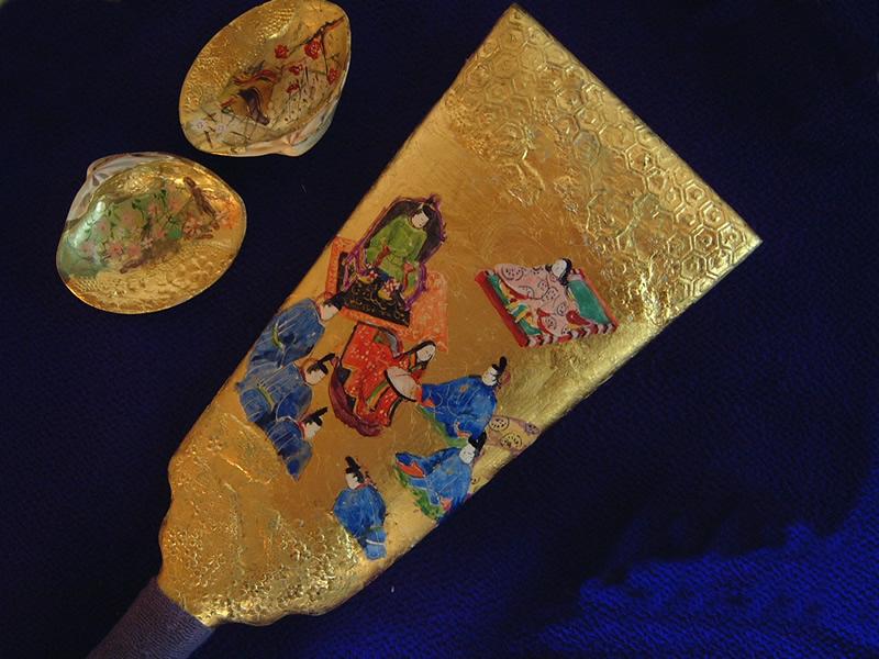 【物語の解説】源氏は12歳になった春、京の清涼殿でその元服の儀が盛大に行われ、奥の玉座には帝が座り、右手には若宮(源氏)がすわり儀がおこなわれようとしている場面です。(金箔、顔彩仕上げ、羽子板立て、桐箱入り)