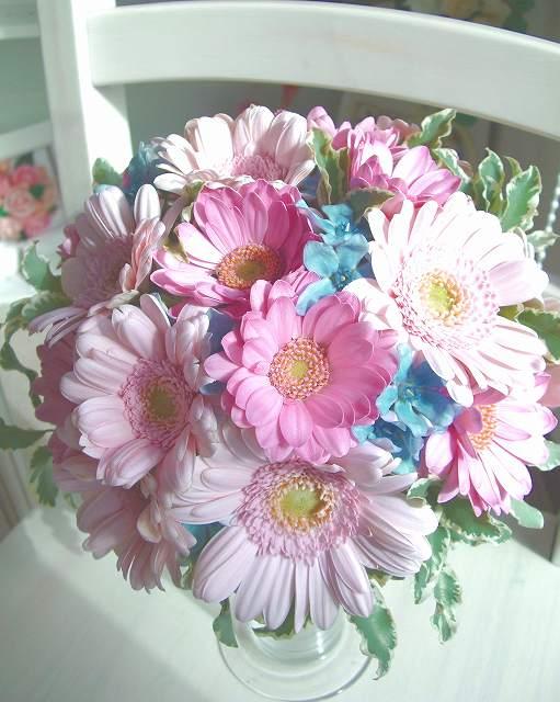淡いピンクと、濃いめのピンクのガーベラに、キュートな星型のブルーの小花をちりばめたプリプリにかわいいラウンドブーケ。色ドレスはもちろん、白ドレスのイメチェンアクセにぴったりのおススメブーケがブートニアとセットで「今月の格安ブーケ」に登場!<br>8000円(税別)でブートニア付き★<br>全国郵送可。