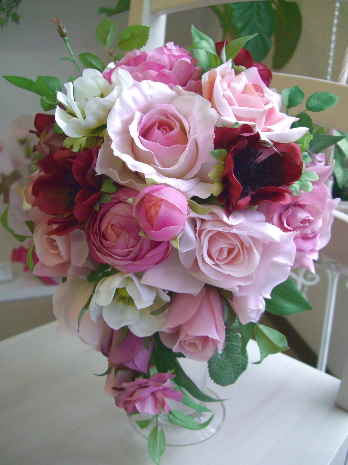 ピンク系~赤のグラデーションに仕上げた可愛らしいティアドロップブーケ。淡いピンクと、濃い目のピンクがバランスよく配されて、ドレスの優しいアクセントにピッタリ。ドレスが華やか系の花嫁さんは、ブーケはあまりコエコテにせず、配色だけで、バランスをとると美しく仕上がります。<br>そこら辺のアドバイスは、弊社へお任せ下さい!<br>ブートニア込みで13000円(税別)。配色の調整や、長さの調整ももちろんOk!ピッタリに仕上げます。