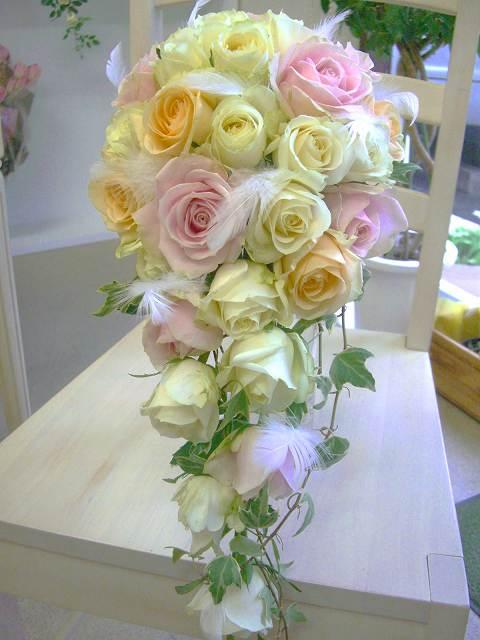 オフホワイトローズに、淡いピンクや、アプリコットのバラをふんだんにモコモコとデザインして、豪華でプリプリに可愛いキャスケードに仕上げました。オフホワイトのドレスを選んだ花嫁さんにピッタリ。また、天使の羽を所々に配して、歩くたびに動く様子は、愛らしく清楚な花嫁を演出します。