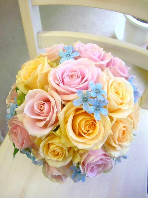 パステル色の生花のバラをみっちりと可愛らしく。ブルーの星型の小花がキュートなアクセント。サムシングブルーの星型は、さりげなく、愛らしく。ドレスの色は、ピンク系でも、サーモン系でも、黄色系でも、もちろんブルー系のアクセントにもピッタリ。
