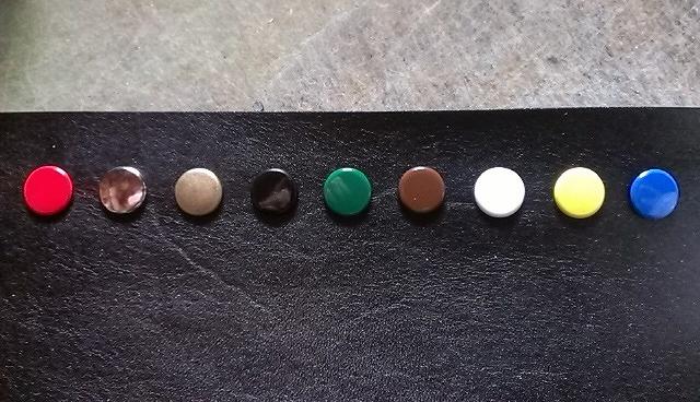 ボタンの色見本です。左から赤、ニッケル、アンティーク、黒、緑、茶、白、黄、青です。