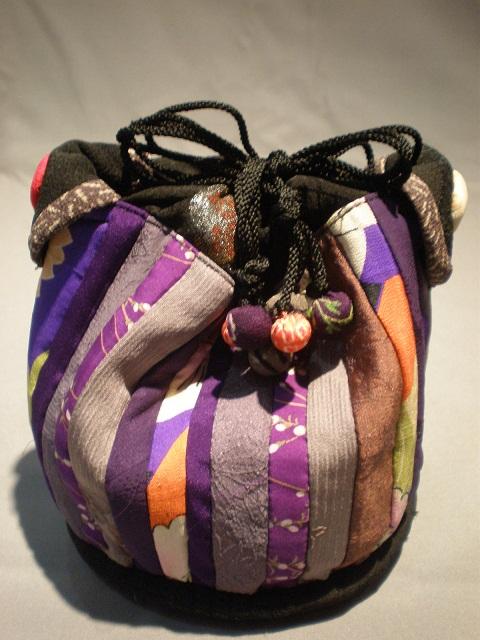 縮緬と絹で大正ロマン風に仕上げてみました。紐の玉はすべて縮緬で、中は厚手のしっかりした絹を使用しています。  生 地:古布 サイズ:高さ17cm×幅23cm 送 料:無料