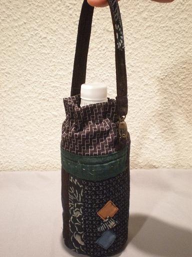 絣に深緑色の綿古布がポイントです。紐留めは中国の算盤の玉。「襟」を高めに仕上げた商品です。  生 地:古布(絣など) サイズ:500ccペットボトル用 送 料:無料