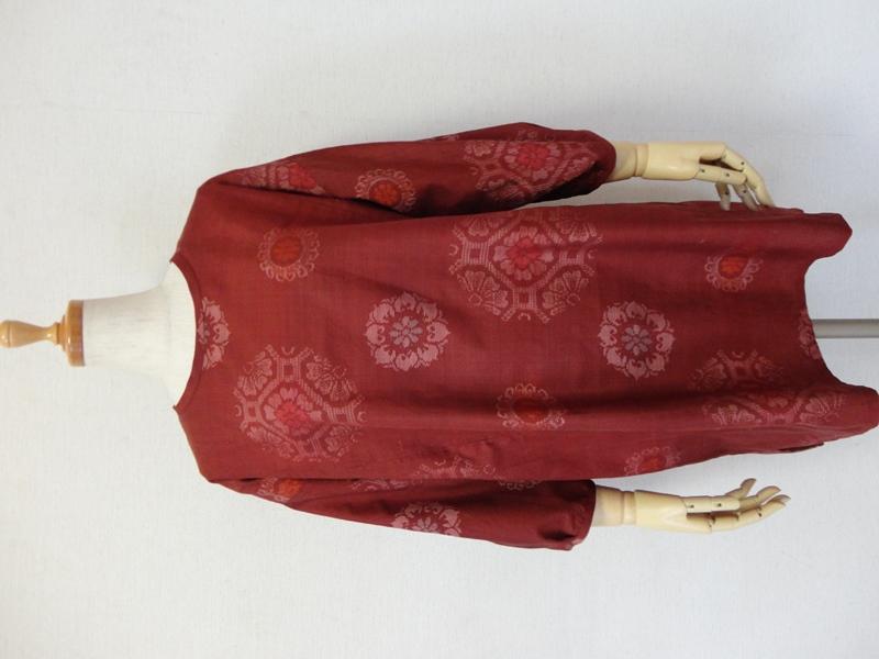 """<p>sold out ありがとうございます<br>古い紬の着物からチュニックワンピースを作りました。ボルドーの地色に色々な華文様が可愛い紬です。<br>紬の種類は分かりかねますが正絹で織り傷はありますがしっかりした生地です。<br>ドロップショルダーで裾は後ろが長く、横スリットはアール型です。<br>襟周りと袖口周りはパイピングで始末しています。<br>後ろスラッシュ開きループ掛け(1.15㎝貝ボタン)仕上です。<br>襟ぐりはいつもより狭めで、右脇にシームポケットを付けてありますので便利です。<br>共布でスヌードも付けてあります。お揃いで、冬の差し色として単品でもよいです。<br><font style=""""background-color: rgb(255, 204, 153);"""">※色合いはもう少し暗めです。</font></p><p><font style=""""background-color: rgb(255, 204, 153);""""></font><br></p>"""